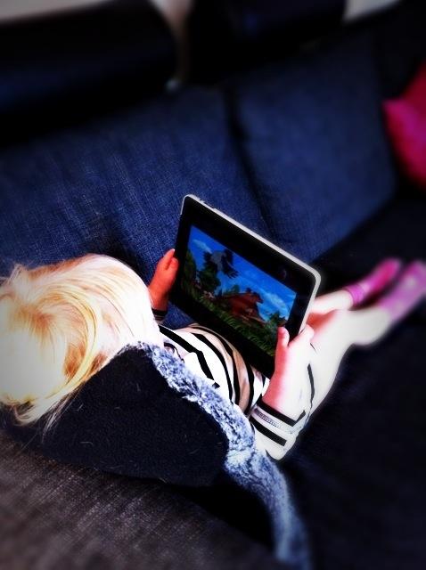 Min dotter Lova sittandes med iPad i knät